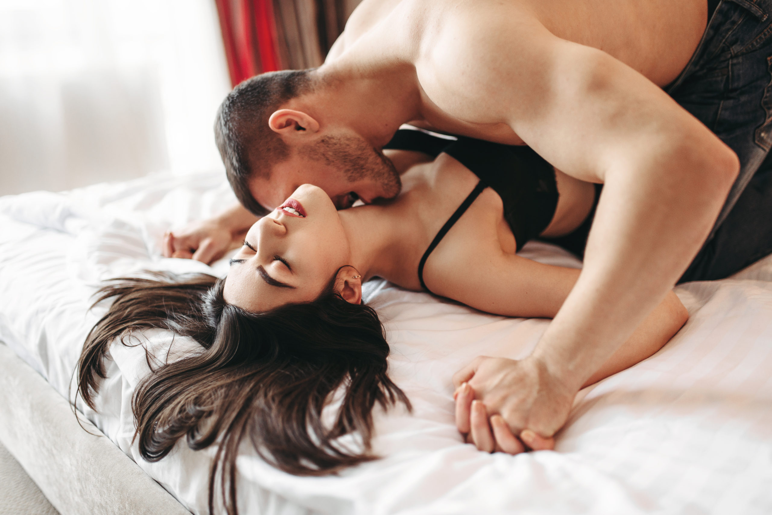 Sexy couple lying and kissing on big white bed